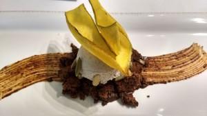 helado de plátano dominico servido sobre un bizcocho suave de semillas de cacao y con un trazo de mole poblano, acompañado de tapioca